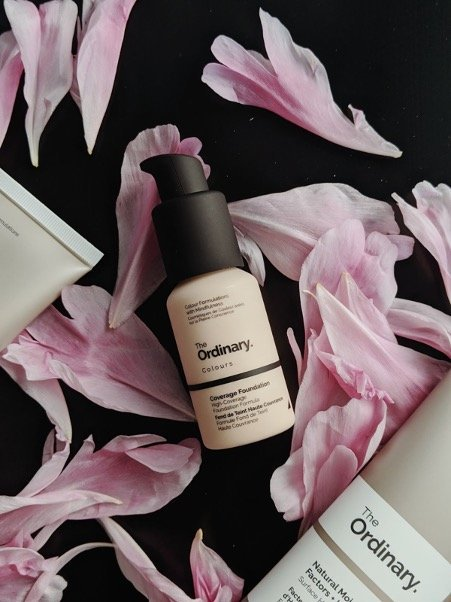 A branded bottle 'the Ordinary' laying on a background with pink flowers