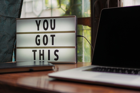 """A laptop and a board with a motivational quote """"You got this"""""""