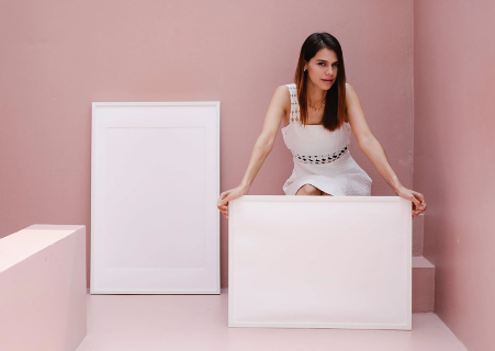 A woman holding a white painting with a pink background