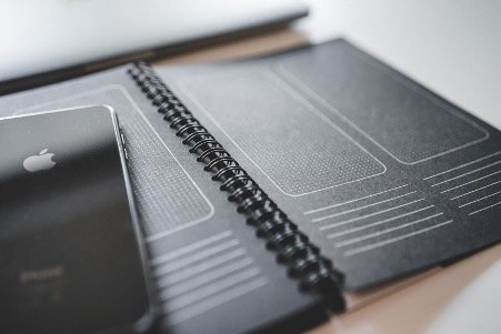 Black UX notepad with an iPhone laying on it